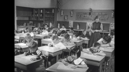 united-states-1950s-teacher-watching-children-in-class-close-up-of-girl-writing-teacher-walking-around-and-making-comments-to-children-in-classroom_b8e6akuqg_thumbnail-full01.png
